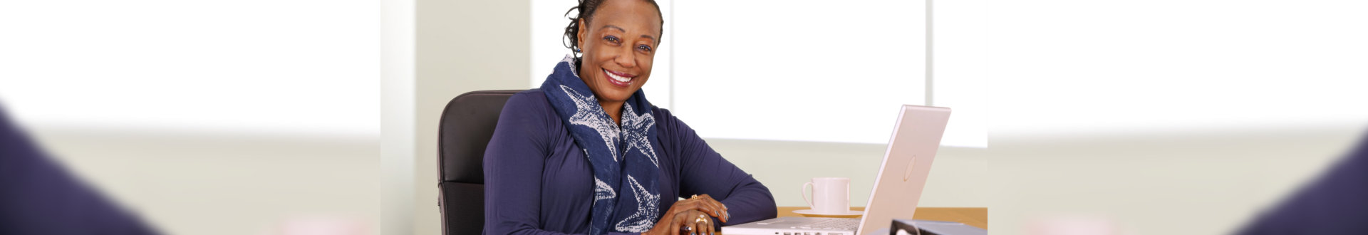 A black businesswoman poses for a portrait at her desk