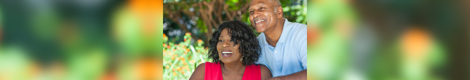 A happy senior African American man and woman couple in their sixties outside together smiling